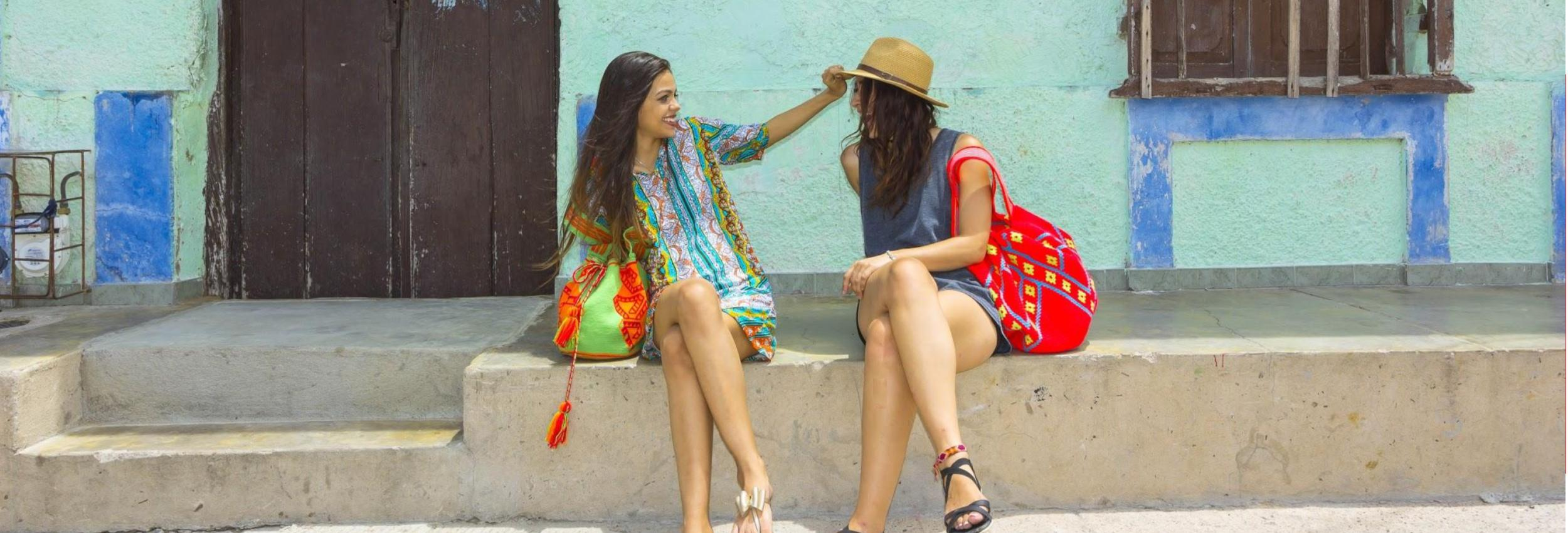 Women sitting on the street with bright colores Wayuu beach bags